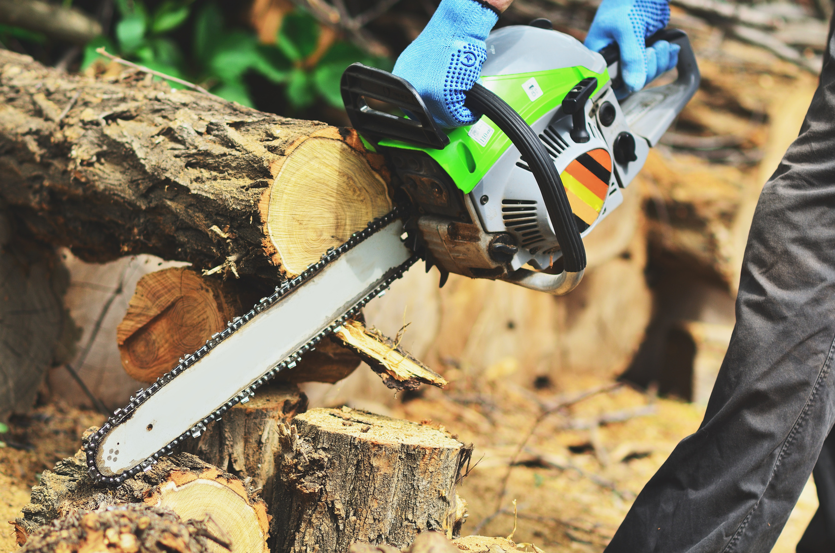 A man in blue mitts cuts a piece of wood from a chainsaw