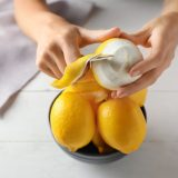 Woman peeling ripe lemons at white wooden table, closeup