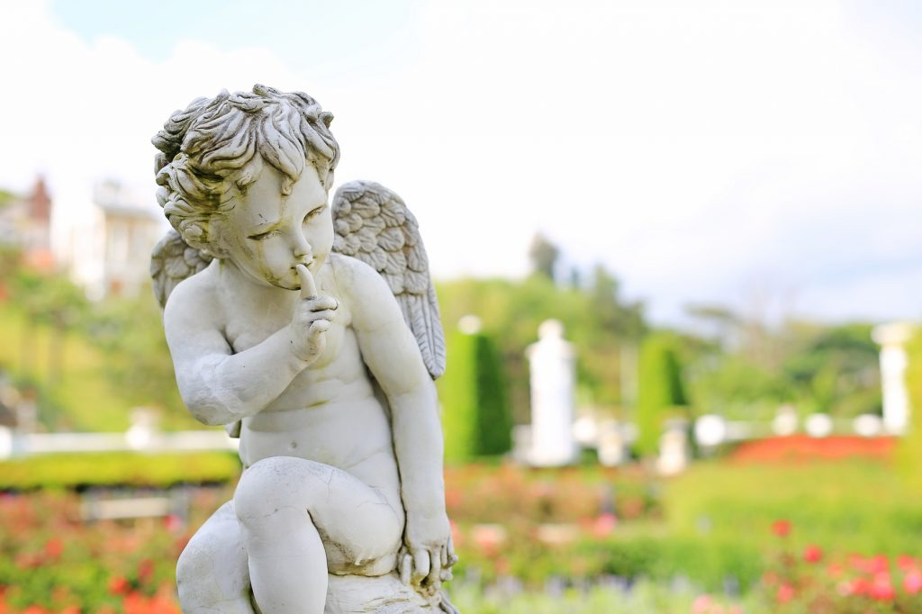 Cupid sculpture in summer garden outdoor.