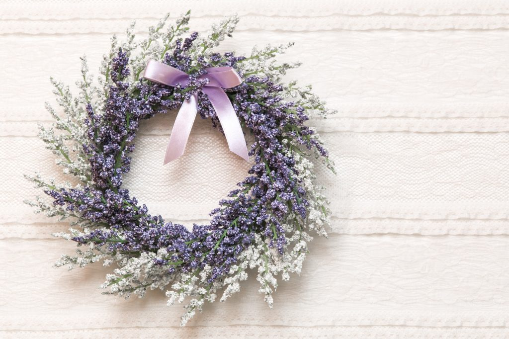 Wreath with lavender flowers on lace fabric background, selective focus